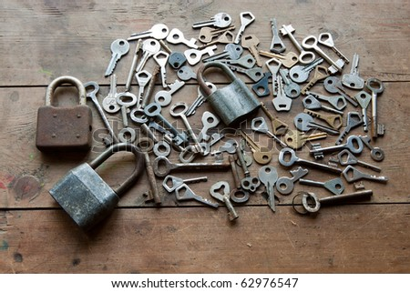 locks and lots of keys on wooden table - stock photo