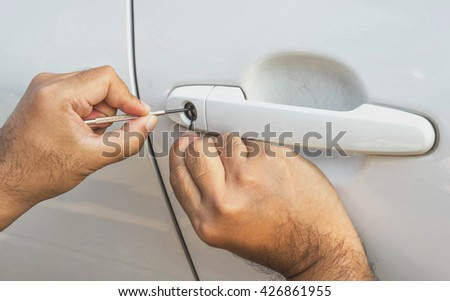 locksmith car will open white car door white screwdriver - selective to focus on key hold - stock photo