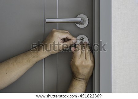 locksmith try to open the door by screwdriver - can use to display or montage on products - stock photo