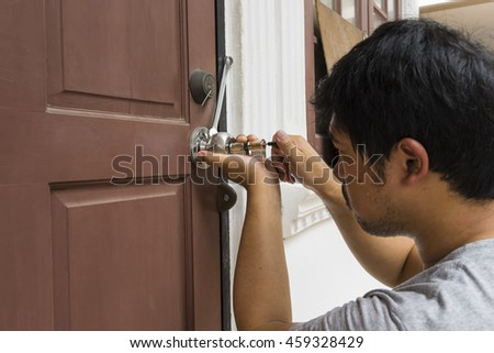 locksmith try to open the old wood door by his tools at home - can use to display or montage on product