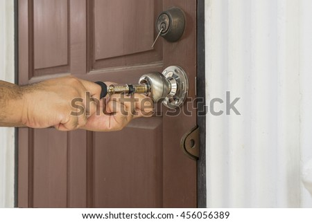 locksmith use his tool open the old wood door - stock photo
