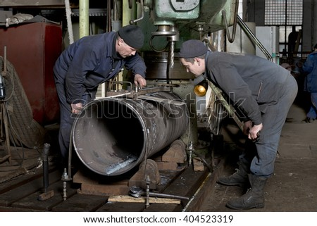 Locksmiths boilermakers on the drilling machine is manufactured piece for boiler