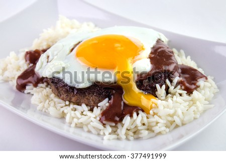 Loco Moco , traditional Hawaiian cuisine , burger patty on rice with a fried egg and brown gravy sauce - stock photo