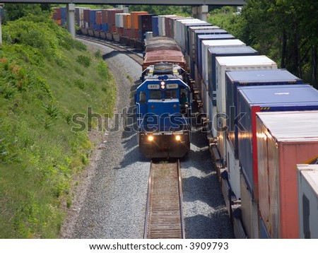 Locomotive pulling short train beside parked container cars - stock photo