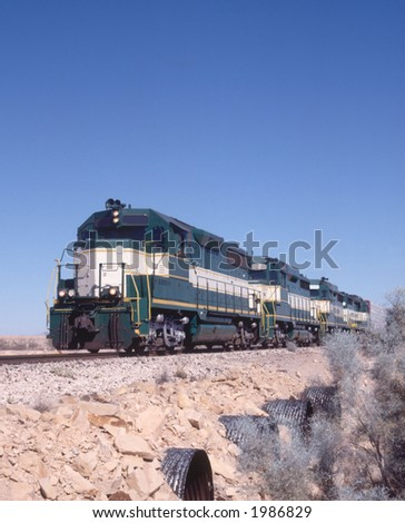 Locomotive with train in desert - stock photo