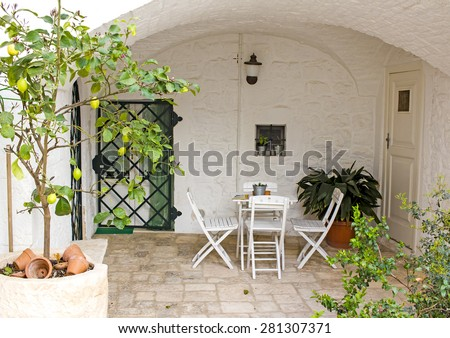 LOCOROTONDO, ITALY - MAY 2 : Cozy patio under a stone vault with potted plants and garden furniture in Locorotondo town, Apulia, southern Italy on May 2nd, 2015 - stock photo