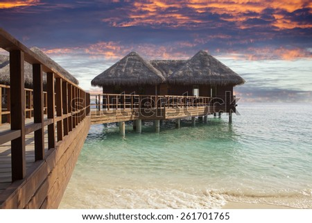 Lodges over water at the time sunset. Maldives.  - stock photo