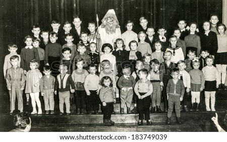 LODZ, POLAND, CIRCA DECEMBER 1970's: Vintage photo of group of children posing with Santa Claus  - stock photo