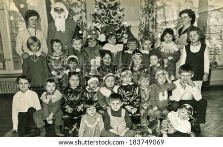 LODZ, POLAND, CIRCA DECEMBER 1970's: Vintage photo of group of little children posing with Santa Claus and their tutors - stock photo