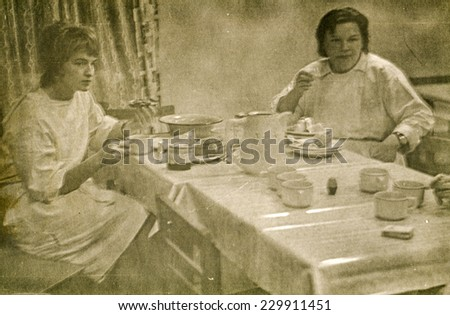 LODZ, POLAND, CIRCA FIFTIES - Vintage photo of two young female doctors eating breakfast in hospital