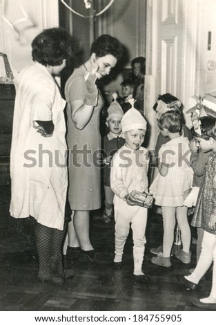 LODZ, POLAND, CIRCA 1970's: Vintage photo of children and their tutors during a Christmas party in kindergarten - stock photo