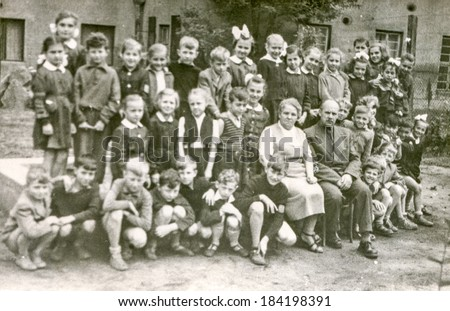 LODZ,POLAND, CIRCA 1950's: Vintage photo of group of  classmates and teachers posing together  in front of the school - stock photo