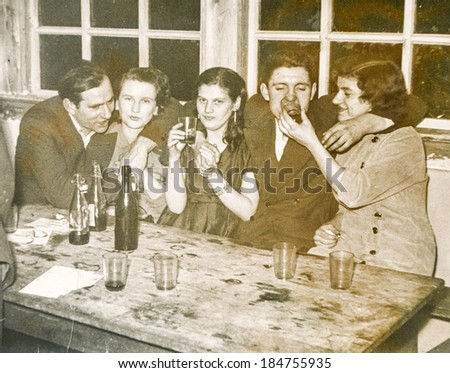 LODZ, POLAND, CIRCA 1950's: Vintage photo of young people parting and drinking alcohol together - stock photo