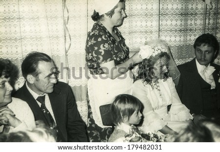 LODZ, POLAND, CIRCA SEVENTIES - Vintage photo of wedding guests and newlyweds - a woman is adjusting a veil of bride
