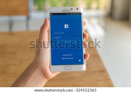 Loei, Thailand - August 7, 2015: Hand holding samsung galaxy note edge with mobile application for Facebook on the screen - stock photo