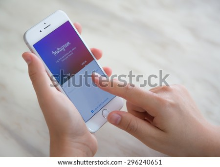 Loei, Thailand - July 12, 2015: Hand holding Iphone with mobile application for Instagram on the screen - stock photo