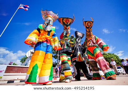 "Loei, Thailand - June 13, 2010 : People are dressing with colorful clothes and put the hand made mask which made from wood or threshing bamboo in ghost mask festival or ""Pi Ta Khon"""