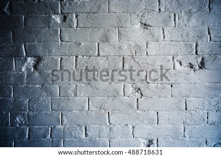 Loft styled white brick wall grunge brick wall under a thick layer of white plaster from plaster background. Brick wall in white with blue darkened vignette. White brick wall for background or texture
