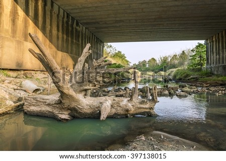 log at Under the bridge : Peaceful and Tranquil nature - river flowing through natural cascades and wet rock and sand with sunlight shining. - stock photo