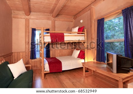 Log cabin bedroom with bunk bed. - stock photo