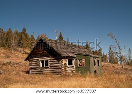 Log cabin in a remote mining area still standing after many years of abandonment - stock photo