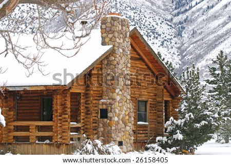 Log cabin in the mountains during the winter. - stock photo