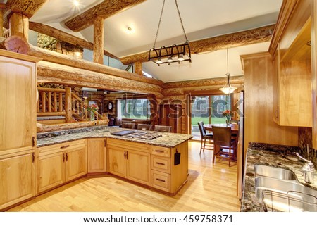Log cabin kitchen interior design with large honey color storage combination and stone counter tops. View of staircase. Northwest, USA