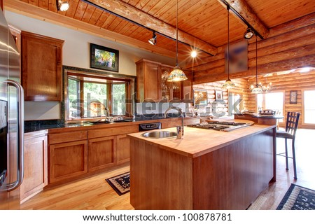 Log cabin large kitchen interior with island. - stock photo