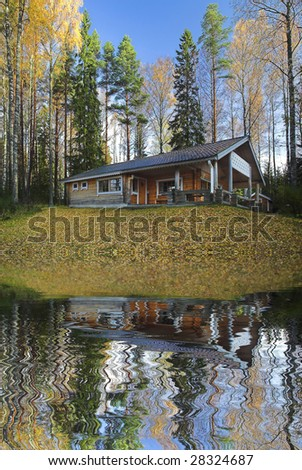 Log cabin on the shore of the lake - stock photo