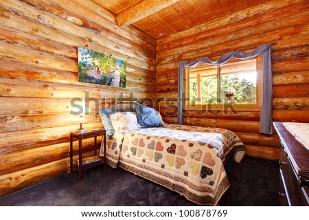 Log cabin rustic bedroom with blue curtains and large logs. - stock photo