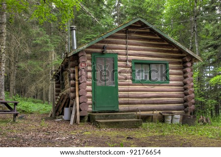 Log cabin surrounded by the forest at Duck Mountain Provincial Park in Saskatchewan, Canada - stock photo