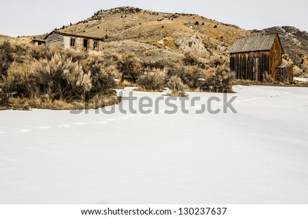 Log home on a hill with a barn or storage building nearby on a winter day at Bannack State Park in Montana.