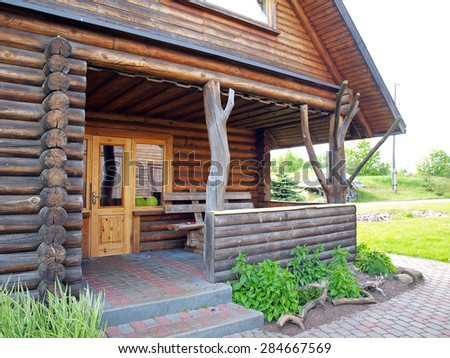 Log house entrance with terrace and concrete brick footpath      - stock photo
