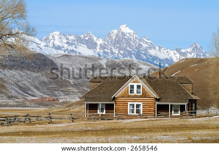 Log House With Snow Covered Mountains in Background - stock photo