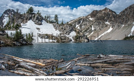 Log jam at outlet to Idaho Sawtooth Lake with blue water and snow capped mountains behind. - stock photo