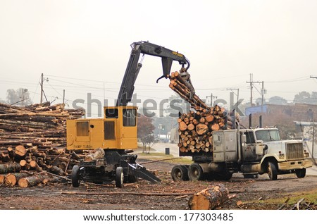 Log loader unloading a truck full of pine pulp wood at a mill in Mississippi - stock photo