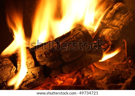 Log on fire with flames in yellow - stock photo