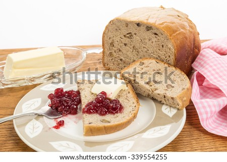 Loganberry preserves spread on slice from fresh loaf of banana nut bread with bright light from back.