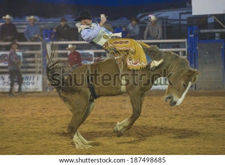 LOGANDALE , NEVADA - APRIL 10 : Cowboy Participating in a Bucking Horse Competition at the Clark County Fair and Rodeo a Professional Rodeo held in Logandale Nevada , USA on April 10 2014  - stock photo