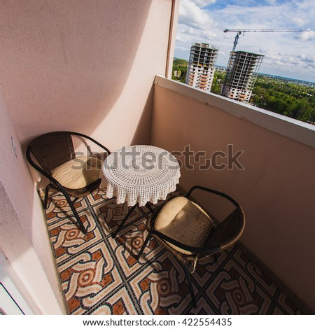 Loggia apartment high-rise building with wicker chairs and a table in the new area which has just built - stock photo