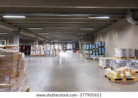 logistic, storage, loading, shipment and equipment concept - forklift loader and boxes at warehouse - stock photo