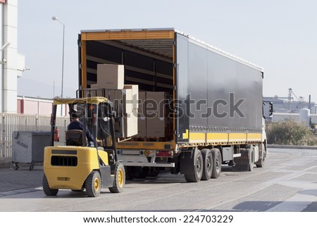 Logistics and Handling. Forklift is loading the truck. - stock photo