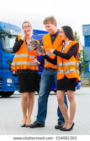 Logistics - proud driver or forwarder and colleagues with tablet computer, in front of trucks and trailers, on a transshipment point, its a good and successful team - stock photo