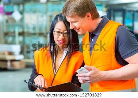 Logistics Teamwork - Worker or warehouseman and his female coworker with tablet computer at warehouse of freight forwarding company - stock photo
