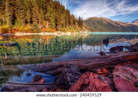 Logs and rocks on the shore of a crisp clear mountain lake - stock photo