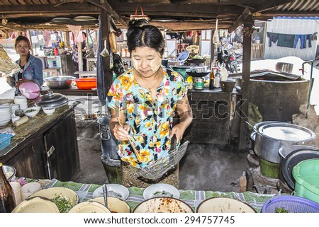 LOIKAW, MYANMAR - FEBRUARY 5, 2015: A woman is serving a noodle soup in a noodle shop at Loikaw, Myanmar