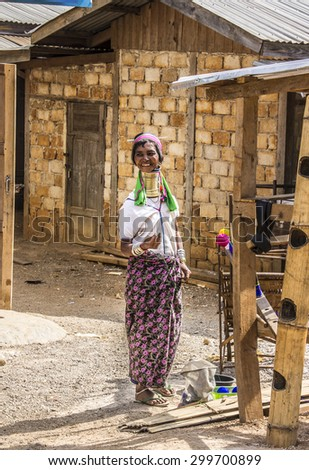 LOIKAW, MYANMR - FEBRUARY 7, 2015: A woman of the Padaung tribe is standing in front of her house at  a street near Loikaw, Myanmar