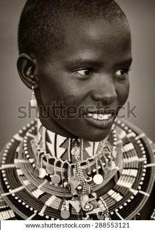 LOITOKTOK - KENYA - JANUARY 5, 2015: Unidentified young beautiful Maasai woman with traditional necklace poses for a portrait on January 5, 2015 in Loitoktok, Kenya. - stock photo