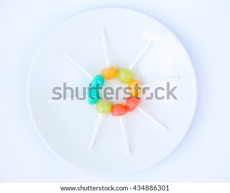 lollipop candies in white plate on white background - stock photo