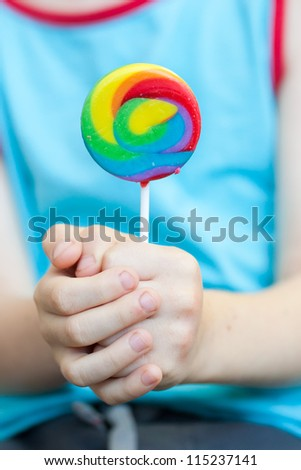 lollipop candy in child hands - stock photo